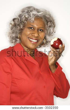 stock photo : Mature adult African American female holding half eaten apple ...