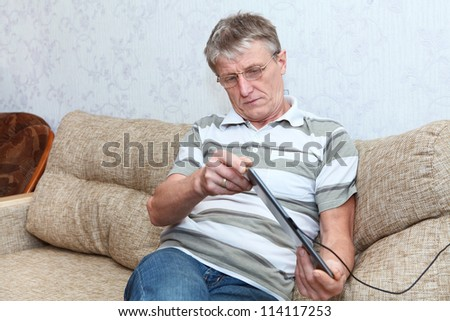 Mature adult Caucasian man researching at a new tablet pc in domestic room