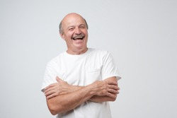 Mature adult man in white tshirt with moustache laughing looking at the camera over white background. Some jokes are old but gold. Positive emotion concept
