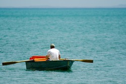 Mature adult man rowing a small wooden rowboat dinghy over calm sea ocean water. Real people. Copy space