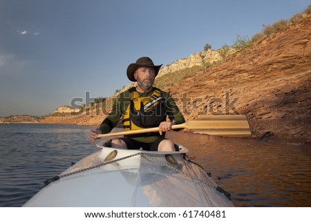 stock photo : mature adult paddler in an expedition decked canoe on calm ...