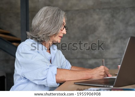 Mature adult 60s business woman working at laptop watching videoconference webinar. Business lady e learning online computer classes, writing in notebook.