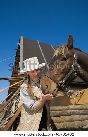 Mature adult woman feeding  her horse at farm