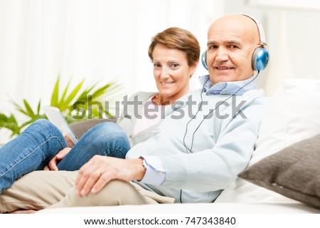 Mature affectionate couple relaxing together on a sofa at home listening to music on headphones #747343840