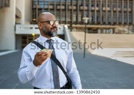 Mature african businessman eating sandwich outdoor. Senior entrepreneur standing outside office building, looking away while enjoying vegetable sandwich. Business man having lunch on the move.
