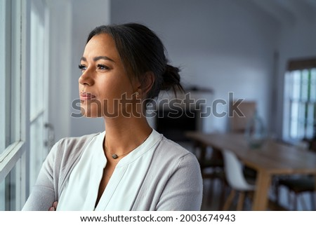 Mature african woman looking outside window with uncertainty. Thoughtful mid adult woman looking away through the window while thinking about her future business after pandemic. Doubtful lady at home.