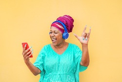 Mature african woman using smartphone app for creating playlist with rock music - Senior female having fun with mobile phone technology - Tech and joyful elderly lifestyle concept - Focus on face