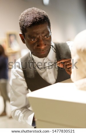 Mature afro man visiting exposition of Art Museum with exhibits of antiquity