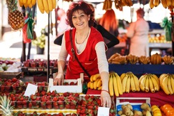 Mature age fruit market saleswoman selecting fresh fruit and preparing for working day.