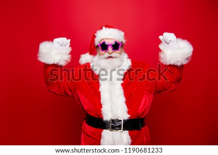 Mature aged confident stylish trendy crazy Saint Nicholas with white beard in costume and star modern disco spectacles raised hands fists up isolated on december noel red background #1190681233