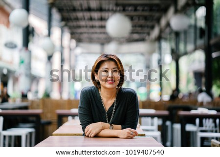 Mature and attractive Asian woman (Korean, Chinese, Japanese) woman leaning against a table in a city in Asia and smiling. She is elegant and professionally dressed.