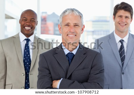 Mature and smiling director standing upright in front of his laughing executives