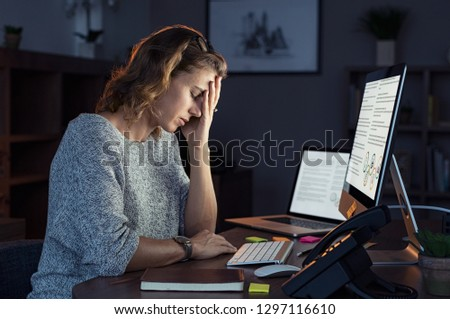Mature and tired businesswoman working on computer until night. Portrait of a casual stressed lady with headache at desk. Exhausted business woman working late night at laptop in office.