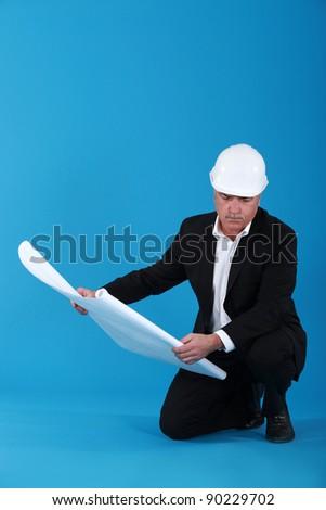 mature architect with blueprints