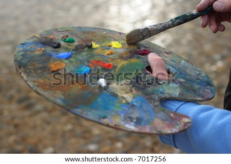 Mature artist with palette and brush painting a coastal landscape focus on brush.