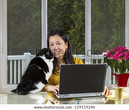 Mature Asian woman and family cat cuddling while working at home with large windows in background