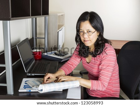 Mature Asian woman  angry doing income taxes with tax form booklet, calculator, coffee cup and computer on desk - stock photo