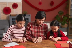 Mature Asian woman spending time with her daughters at home making paper cranes to decorate room for Chinese New Year celebration