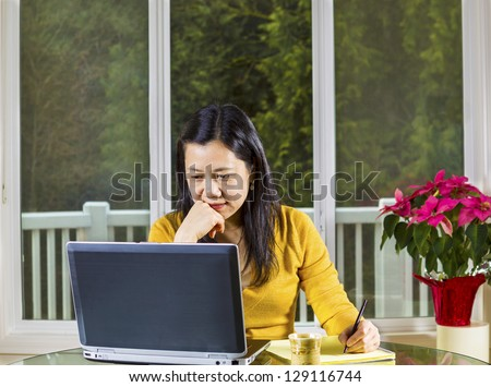Mature Asian woman working at home with notebook computer on glass table with large windows in background