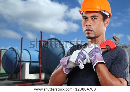 Mature asian worker with a wrench.