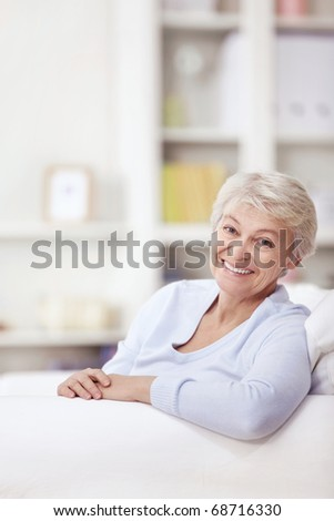 Mature attractive woman on the couch at home