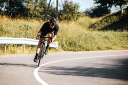 Mature bearded cyclist in sport outfit and protective helmet riding bicycle on fresh air. Sportsman leading active lifestyle with green nature around.