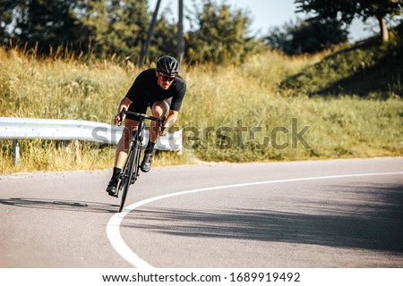 Mature bearded cyclist in sport outfit and protective helmet riding bicycle on fresh air. Sportsman leading active lifestyle with green nature around. Foto d'archivio ©
