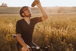 Mature bearded man in sport clothing sitting on his bike and drinking water from black bottle. Active cyclist  in helmet and eyewear feeling thirsty after long race.