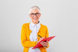 Mature beautiful smiling woman in glasses holding pen, isolated on background. Business concept with clipboard and document in hands