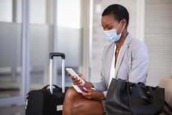 Mature black businesswoman using mobile phone at the airport in the waiting room while wearing face mask due to covid-19. African business woman holding passport and boarding pass typing on smartphone