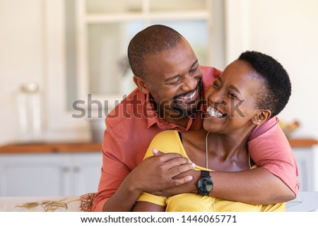 Mature black couple embracing on sofa while looking to each other. Romantic black man embracing woman from behind while laughing together. Happy african wife and husband loving in perfect harmony.