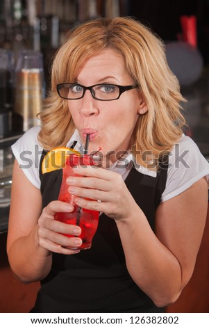 Mature blond female sipping drink with a straw