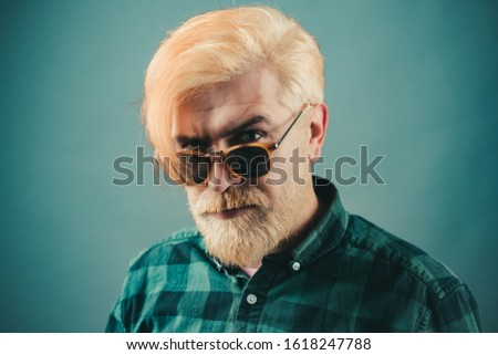 Mature blonde bearded guy with trendy hairdo in casual shirt smiling and looking in camera. Bearded man with fashion sunglasses. Professional model and professional photo shoot
