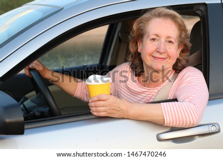 Mature blonde lady driving with coffee