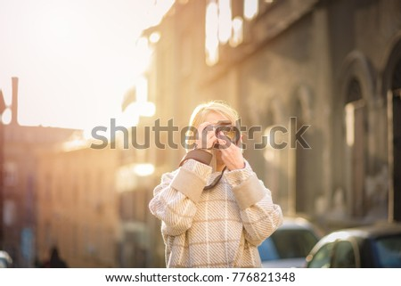 Mature blonde woman, a photographer, taking images of an urban area, tourist or a street photographer