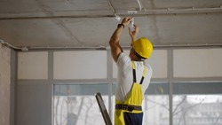 Mature builder using stepladder installing light on the ceiling. Side view of professional construction worker in yellow c helmet and overall twisting light bulb in