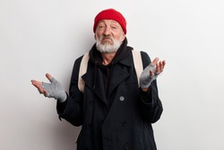 Mature bum, homeless old man with grey beard in coat and red hat shrugs isolated over white background