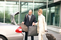Mature business couple on trip loading luggage into car trunk