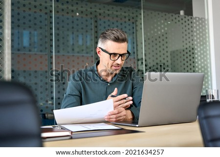 Mature business man executive coach talking using laptop computer having video conference call virtual meeting, professional training negotiation remote working doing online presentation in office.