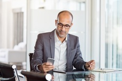 Mature business man in formal clothing wearing spectacles using mobile phone. Serious businessman using smartphone and digital tablet at work. Manager in suit using cellphone in a modern office.