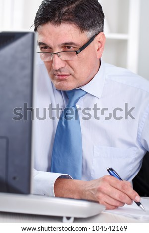 Business man looking at computer screen and working stock photo
