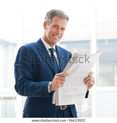 Mature business man reading news and smiling at camera