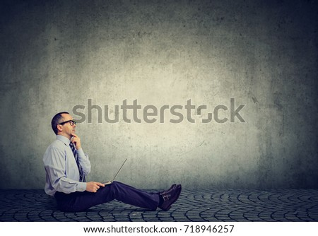 Mature business man with laptop sitting on a floor #718946257