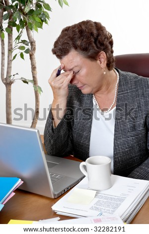 Mature business woman at her desk, eyes closed, worried about bills and financial problems