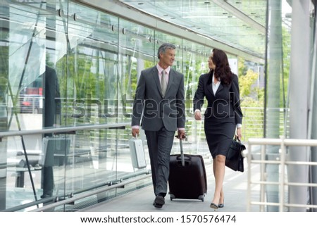 Mature businessman and businesswoman walking with suitcase and briefcases #1570576474