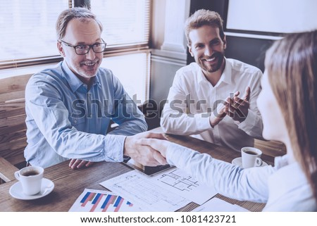 Mature businessman and young business lady are shaking their hands, young man is applauding and smiling while working in office #1081423721
