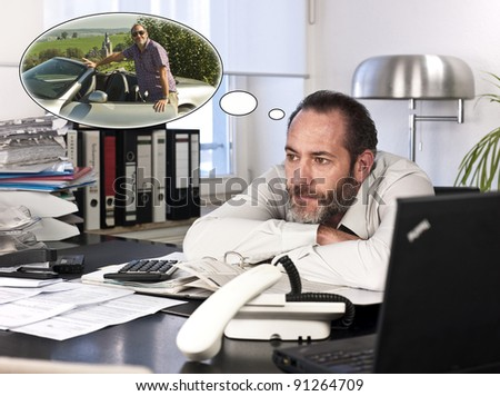 Mature businessman at desk with a thought bubble of himself and new car countryside. Horizontal shot