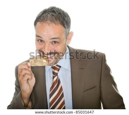 Mature businessman bites his credit card