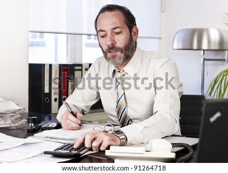Mature businessman calculating finance. Horizontal shot