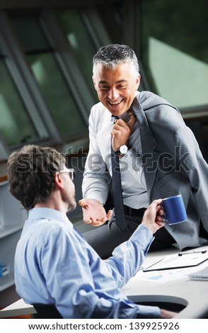Mature Businessman consulting a partner at desk in office
